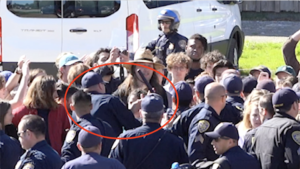 police officers in crowd of students; one officer has his baton raised over Sabrina Shirazi